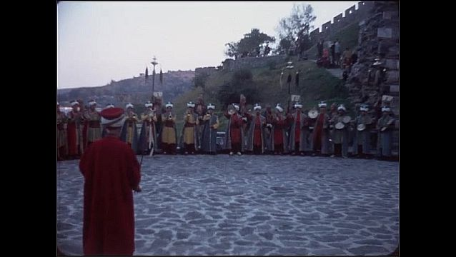 1950s: Men in ceremonial dress stand in circle. Men lift staffs up and down. Men play cymbals, men drum. People watch ceremony.