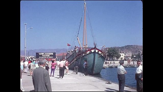1950s: Ship at dock. People walk around on dock. Men stand on boat.