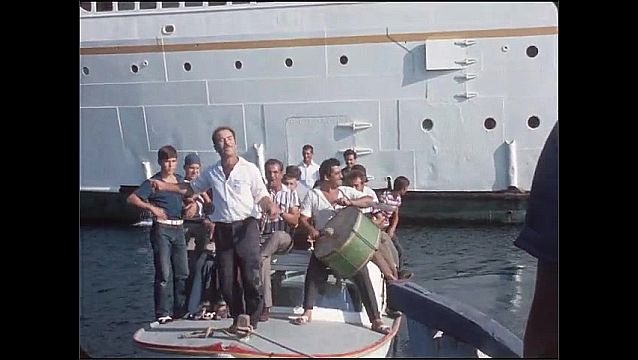 1950s: People on dock, Large cruise ship anchored in water. People stand on small boat, dance and play drums.