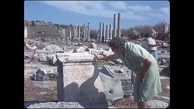 1950s: Ancient ruins. Woman inspects ancient inscription in stone. Ancient ruins with arches.