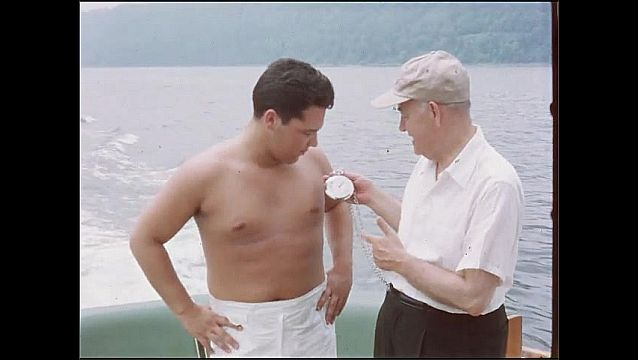 1950s: Men on boat look at pocket watch, man drinks water, takes out cigarette.