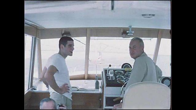 1950s: Man driving boat, pan across men at front of boat. Men talking inside boat. Man playing banjo on boat.