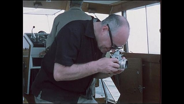 1950s: Man talking inside boat, looks through camera. Man looks through camera.