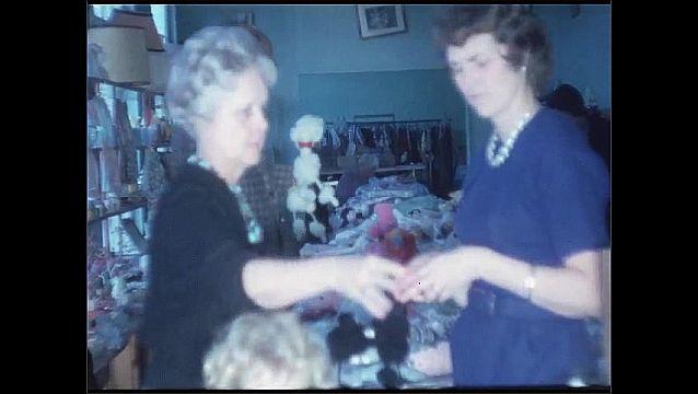 1960s: Women shopping with child. Woman in store. Women looking through bins. Women talking by bin. Items in bin, pan to man shopping.