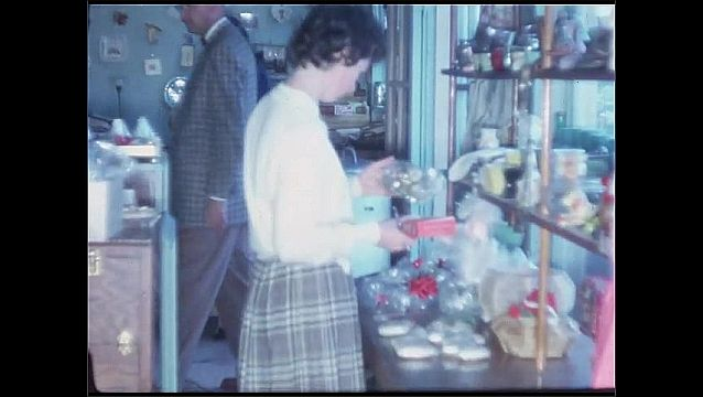 1960s: People in store, woman shows items to camera. Woman shows item to camera, pan to people at register.