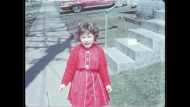 1960s: UNITED STATES: young girl sits on step with cake. Girl smiles at camera outside house. View along street