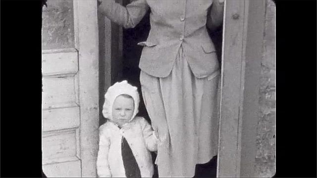 1920s: UNITED STATES: girl in back alley. Lady stands by back door step. Girl and lady on step of house