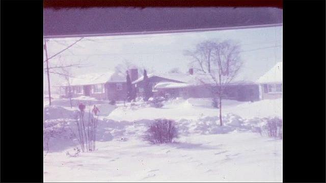 1950s: Man and woman walk up snowy neighborhood street.