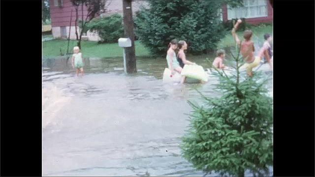 1950s: Children play and wade in water of flooded road. Children ride canoe on flooded neighborhood street.
