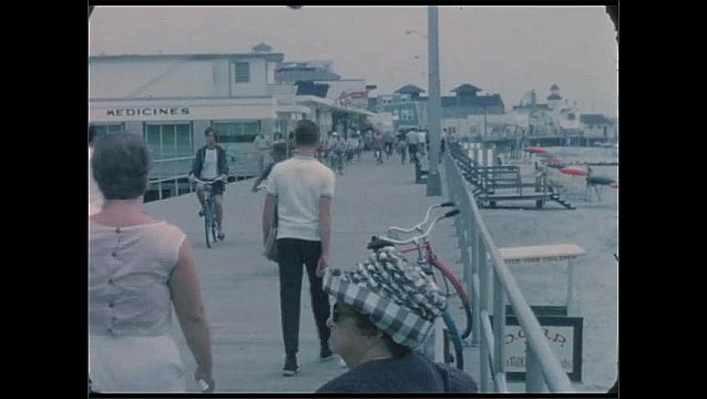 1960s: People walk and ride bicycles on long ocean boardwalk. Woman dives into pool. Flag waves on pole.