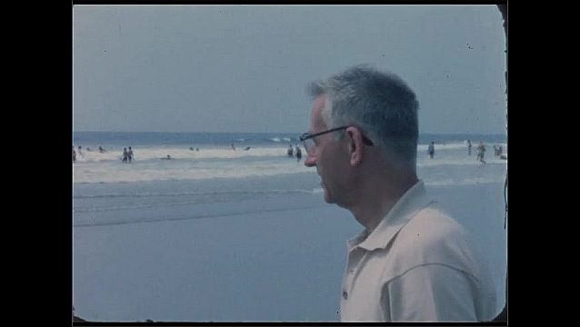 1960s: Man walks on beach near ocean and waves. Man looks out into ocean. People lay and play on beach near wave break.