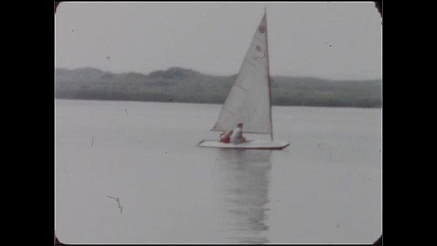 1950s: UNITED STATES: Scotty Warren boat on water. Sailing dinghy on water. Lady and boy on dinghy.