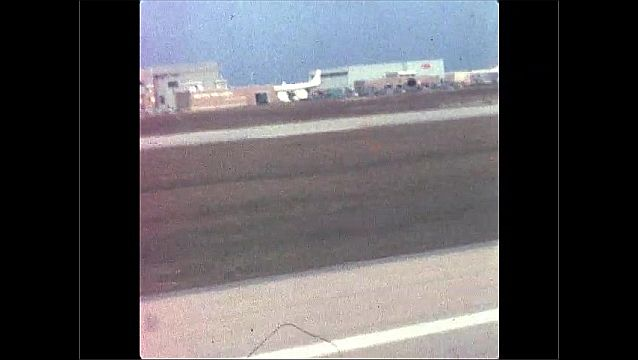 1960s: UNITED STATES: plane on runway. View of airport terminal from window of plane. Plane lands on runway. Plane takes off from runway.