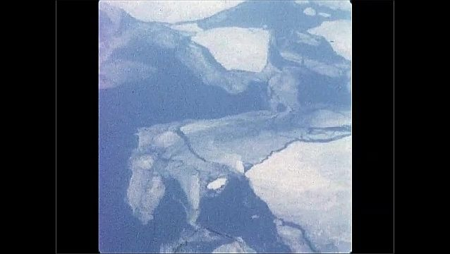 1960s: UNITED STATES: overhead view of city buildings and roads. View from window of plane. Overhead view of lake in landscape. Flight over tundra.