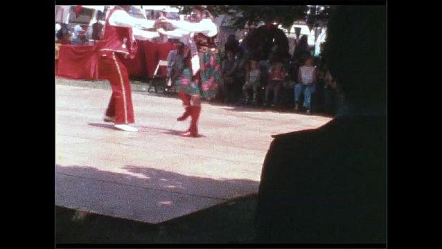 1960s: People dance on outdoor dance floor. Children walk onto dance floor, woman follows children.