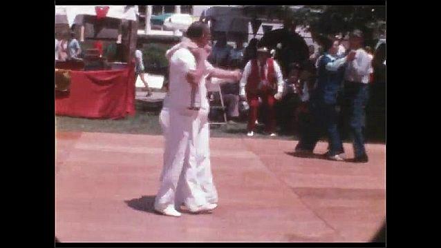 1960s: People dance on outdoor dance floor. Woman stands on dance floor, takes pictures.