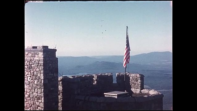 1950s: Mountains. American flag on flagpole at top of mountain. Cars parked on mountain road. People walk along road.