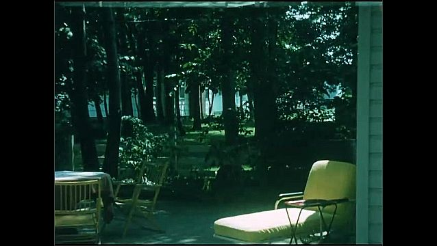 1950s: Lake, trees, mountain, boathouse. Outdoor furniture. Car parked at house.