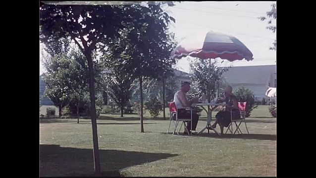 1950s: House and yard. People sit and eat at outdoor table. Women sit outside and have tea.