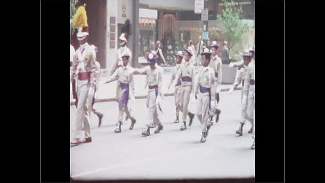 1960s: Men and children in military uniforms carry flags and banners in parade. Children and men carry banner in parade. Women in drill team march in place and carry flags.