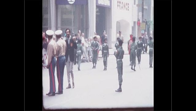 1960s: Boys in military uniforms carry flags and dance in parade. Men in marching band play drums.