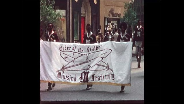 1960s: African American men in Native American headdresses carry banner in parade. Men in college letter sweaters carry banner and march in parade.