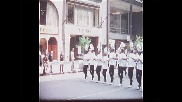 1960s: Girls in uniform carry flags and march in parade. Marching band plays drums and carries instruments in parade.
