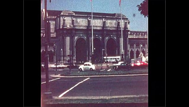 1960s: Cars and trucks drive past fountain and museum in New York City.