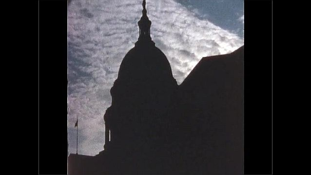 1970s: UNITED STATES: clouds over building. Outline of dome on building. View through park in Autumn.