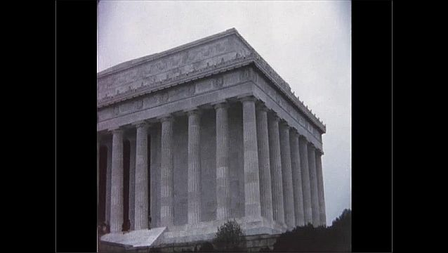 1970s: UNITED STATES: people walk up steps towards columns on building. Gardens by building.