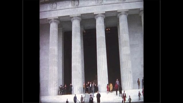 1970s: UNITED STATES: columns and front of building. People walk up steps. Statue of president.