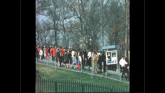 1970s: UNITED STATES: people attend remembrance service at graves. People in park.