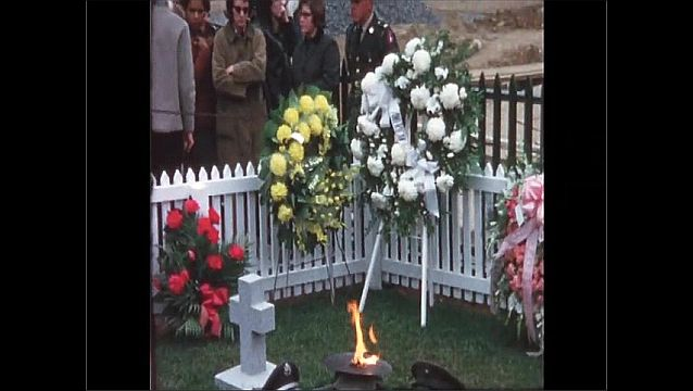 1970s: UNITED STATES: flame in cemetery at service. Flowers at service