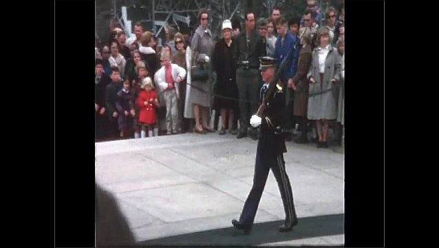 1970s: UNITED STATES: children attend memorial service. Man with rifle at ceremony.