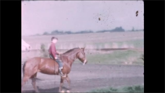 1960s: UNITED STATES: boys ride horses in field by home.