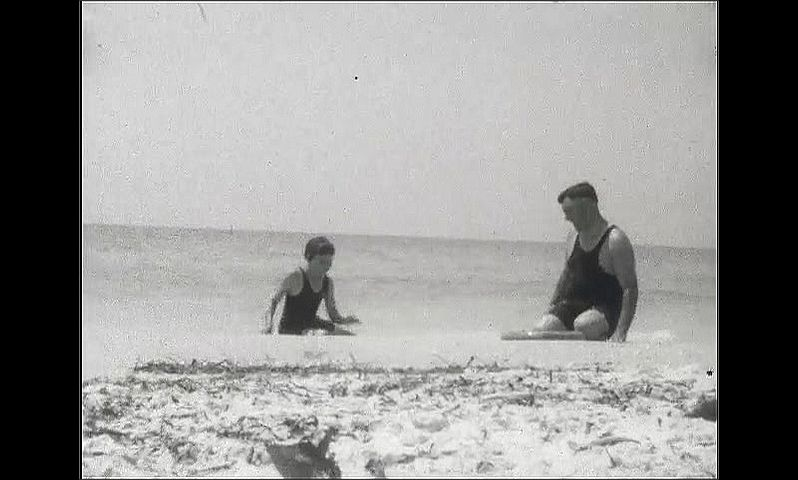 1920s: UNITED STATES: man in sea with child. Father and child have play fight in sea.