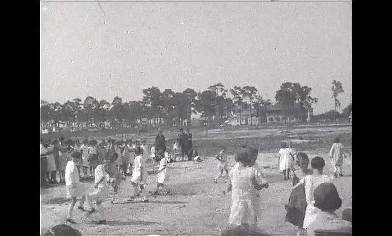 1920s: Audience watches children dance and perform in field. Children dance together and in circles in field.
