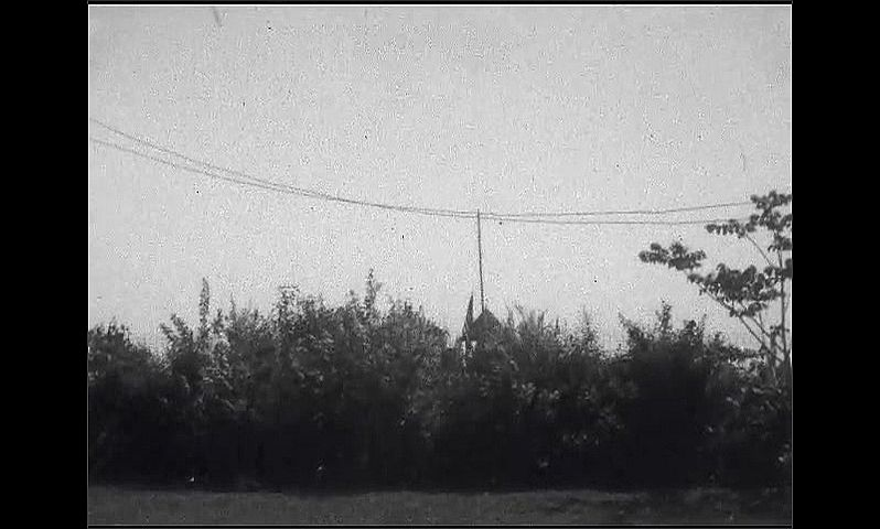 1920s: Blimp flies over rural area. Blimp flies over trees and flagpole.