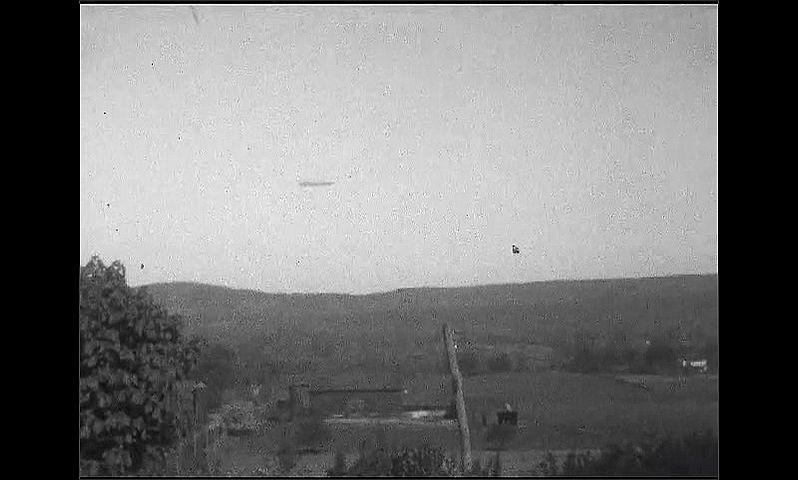 1920s: Blimp flies over rural area. Blimp flies over rolling hills in rural landscape.