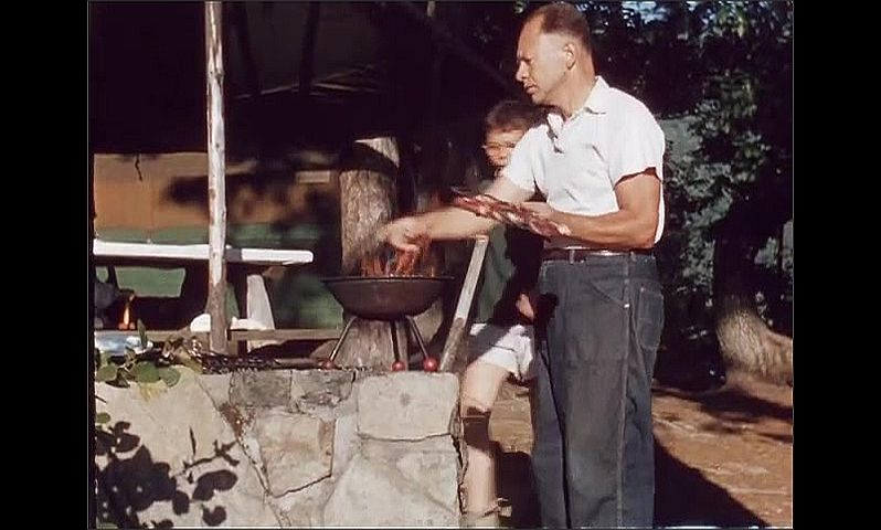 1960s: Man holds steaks over flames in grill at picnic shelter. Man points and boy hands him a plate. Woman washes utensils in bowl of water.