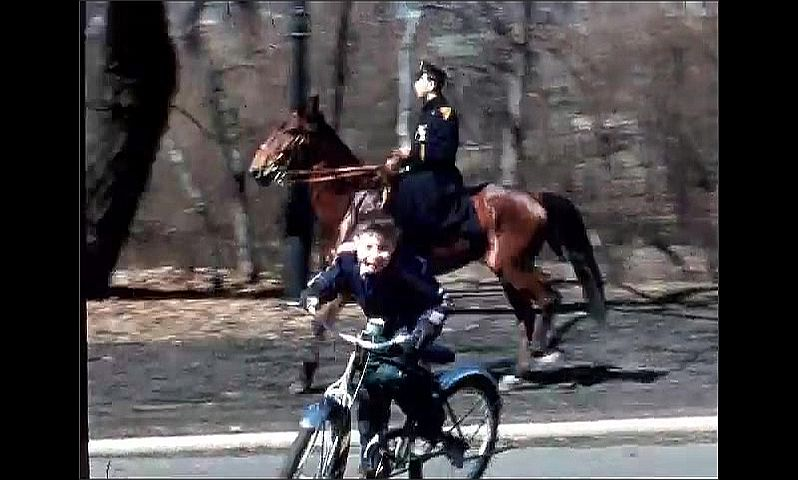1950s: Boy rides bike past mounted police officer on horse at wooded park. Cars line street in newly constructed suburb.