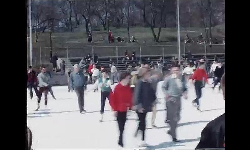1950s: Families ice skate on frozen lake in public park. People watch families skate on frozen rink near building in park.