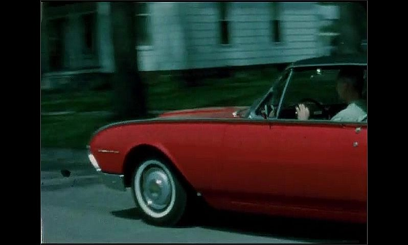 1960s: UNITED STATES: car drives slowly around road in suburb. Red car drives along street. Car turns into road