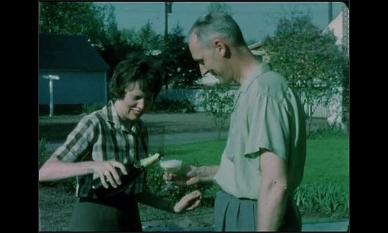 1960s: UNITED STATES: lady pours glass of wine for man. Man drinks from glass