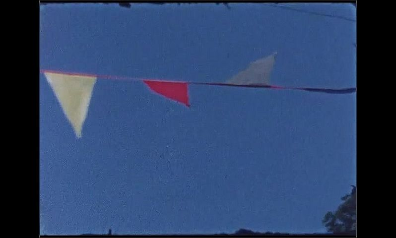 1960s: UNITED STATES: cars and bunting over road. Bunting and blue sky. Poster of clown.