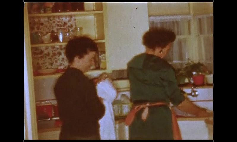 1950s: UNITED STATES: girl poses for camera. Ladies wash and dry dishes in kitchen. Toddler walks around room