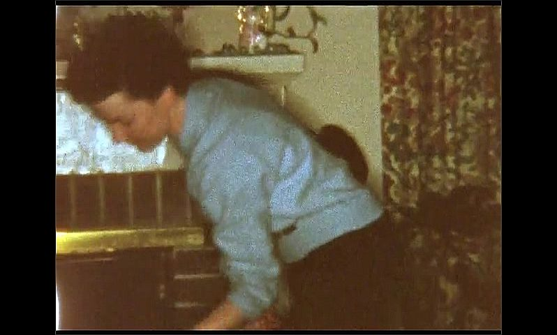1950s: UNITED STATES: log fire in room. Lady with slip of paper.