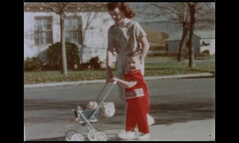 1950s: UNITED STATES: girl and toddler push toy pushchair along pavement by road. Children play outside house