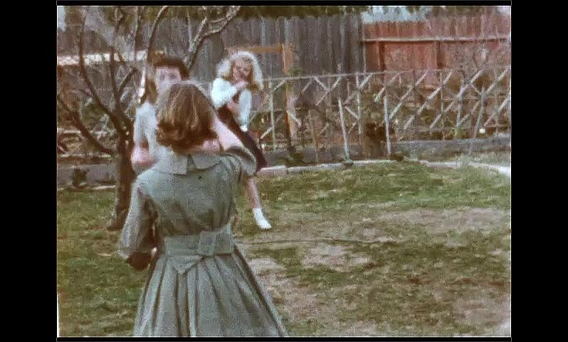 1950s: UNITED STATES: girls play with skipping rope in garden. Girl turns and jumps rope.