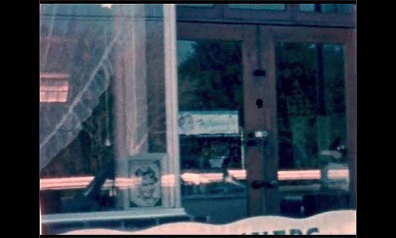 1950s: UNITED STATES: net curtains in beauty salon window. Lady in salon